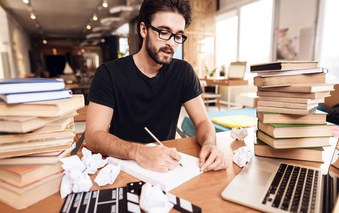copy writer with books around and laptop in front of him