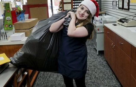 An employee with a plastic bag on her back and santa hat on head