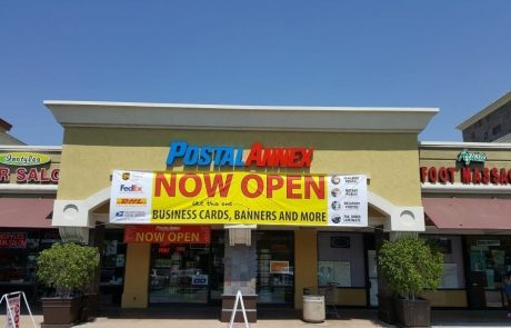 """PostalAnnex Store front with """"Now Open"""" banner hanging under it fascia sign."""